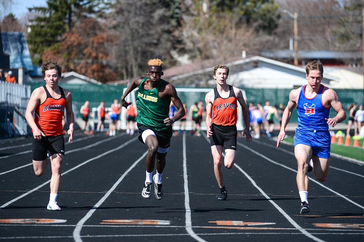 From left, Flathad's Nate Prieto, Whitefish's Marvin Kimera, Flathead's Sam Hopp and Bigfork's Joseph Farrier compete in the 100 meter dash during a track and field meet at Legends Stadium on Tuesday. (Casey Kreider/Daily Inter Lake)