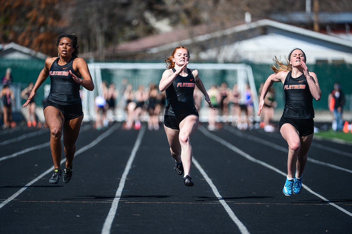 From left, Flathead's Akilah Kubi, Skyleigh Thompson and Kelcey Copping compete in the 100 meter dash during a track and field meet with Whitefish and Bigfork high schools at Legends Stadium on Tuesday. (Casey Kreider/Daily Inter Lake)