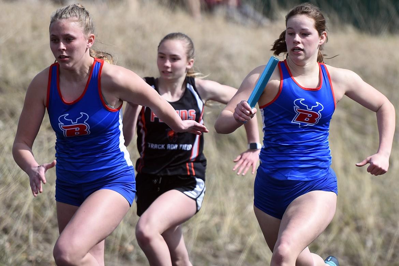 Relay runners race around the track at Bigfork High School. Jeremy Weber/Bigfork Eagle