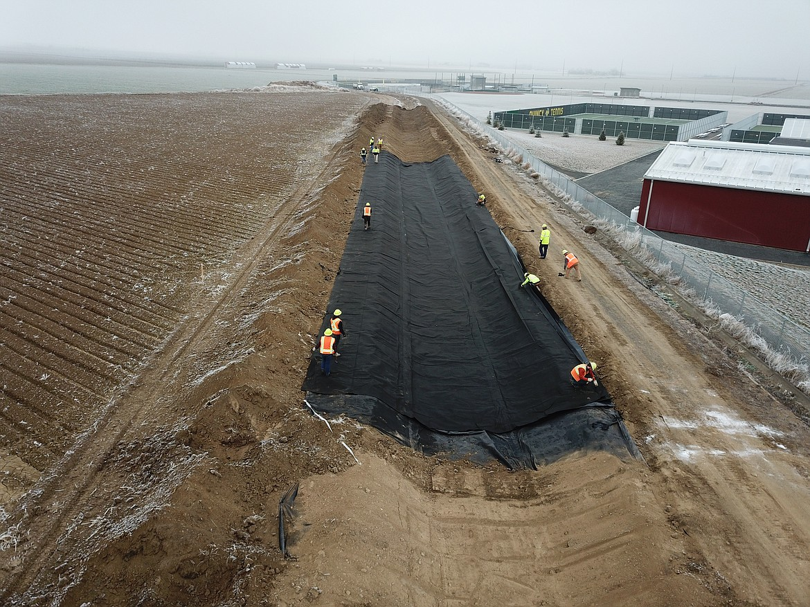 Workers with the Quincy-Columbia Basin Irrigation District install a plastic liner under the W26A tributary canal north of the new Quincy High School campus.