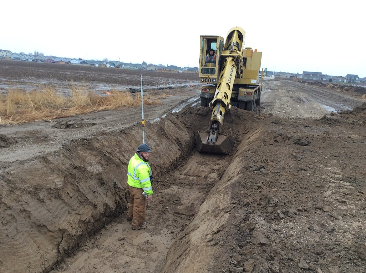 A worker with the Quincy-Columbia Basin Irrigation District oversees the digging of a trench as part of the installation of the W26A17 pipeline.
