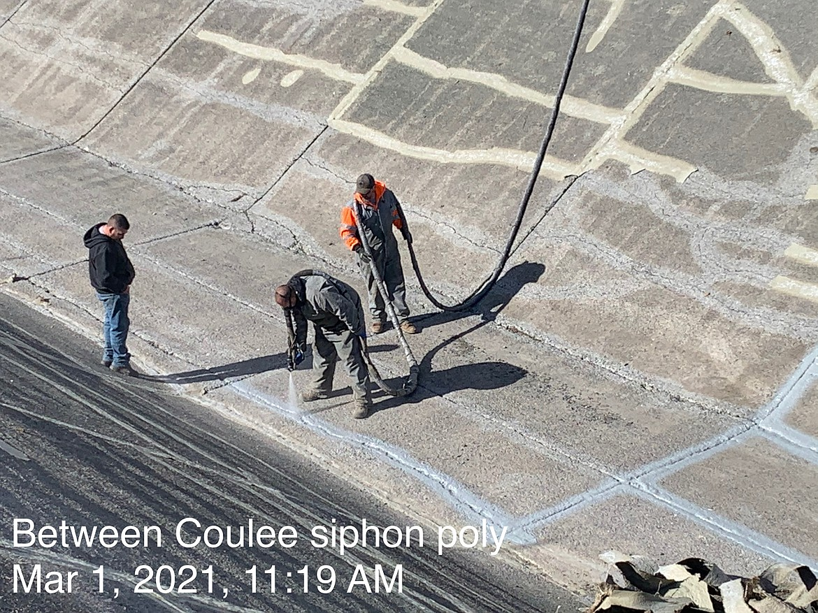 Workers with the Quincy-Columbia Basin Irrigation District seal cracks in concrete near the Coulee Siphon in early March, 2021.