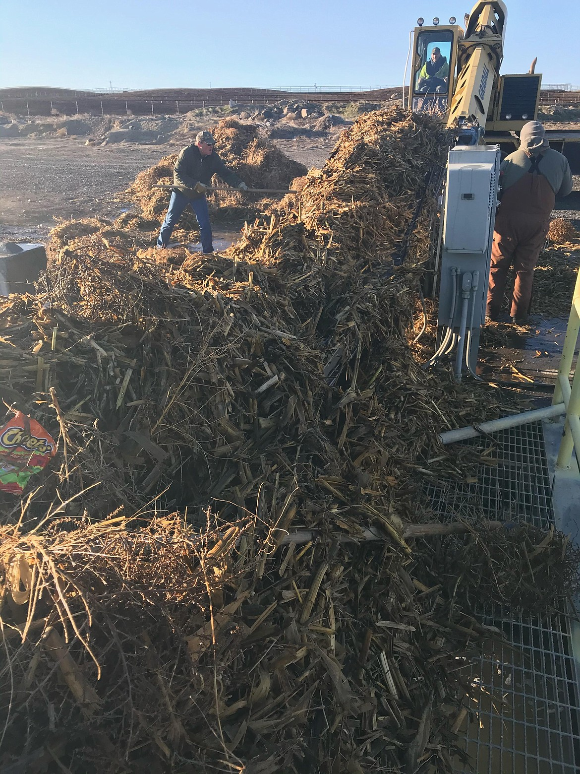 Workers with the Quincy-Columbia Basin Irrigation District clear out weeds, plant debris and trash from an irrigation ditch after a major wind storm in late March.