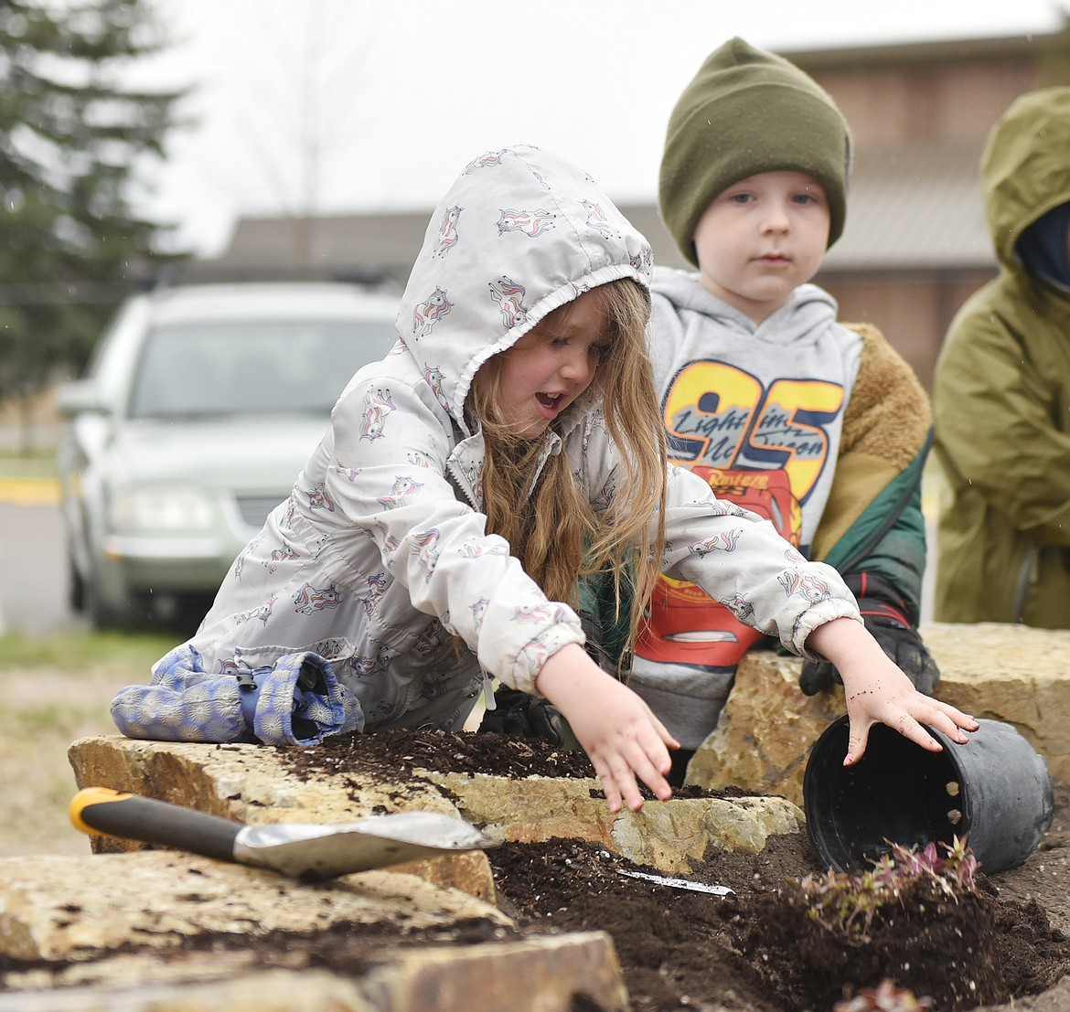 Rylan Frager drops a plant into its spot in the new pollinator garden, while Axel Neville watches. Students from Children's House Montessori School assisted in planting the garden Thursday morning for Earth Day. (Heidi Desch/Whitefish Pilot)