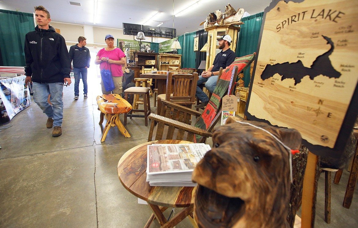 Cody Folda with Wild West Rustic Furniture sits in the center of an array of custom log furniture at the Home and Garden Show at the Kootenai County Fairgrounds on Friday.