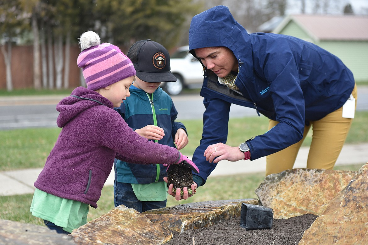 Paige Howard and Hank Gable, with the help of Jennie Bradford with the city Parks and Recreation Department, place a plant in the new pollinator garden at Memorial Park on Thursday. Students from Children's House Montessori School assisted in planting the garden for Earth Day. (Heidi Desch/Whitefish Pilot)