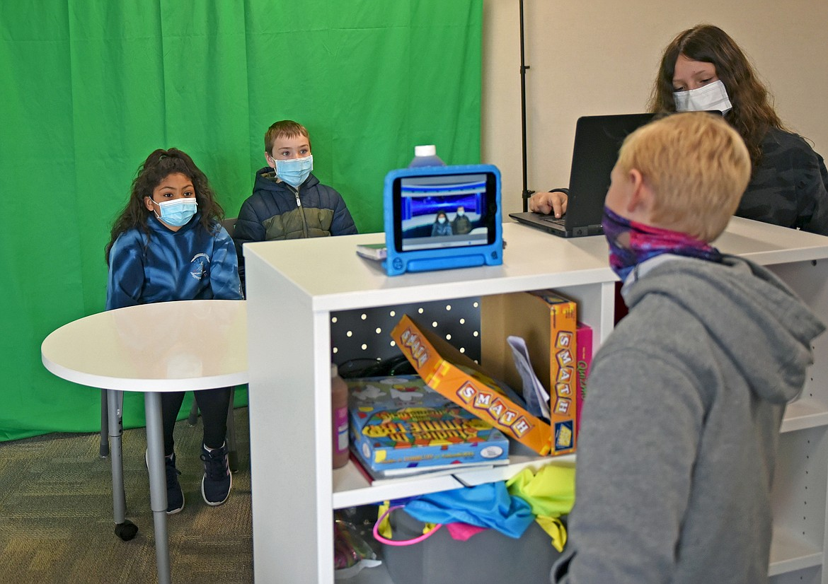 Muldown News anchor Audrey Jones and special reporter Hudson Clark give a report while Kaleb Stevens records them using a tablet and Gianna Mitchell uses a laptop as a teleprompter at the elementary school on Thursday. (Whitney England/Whitefish Pilot)