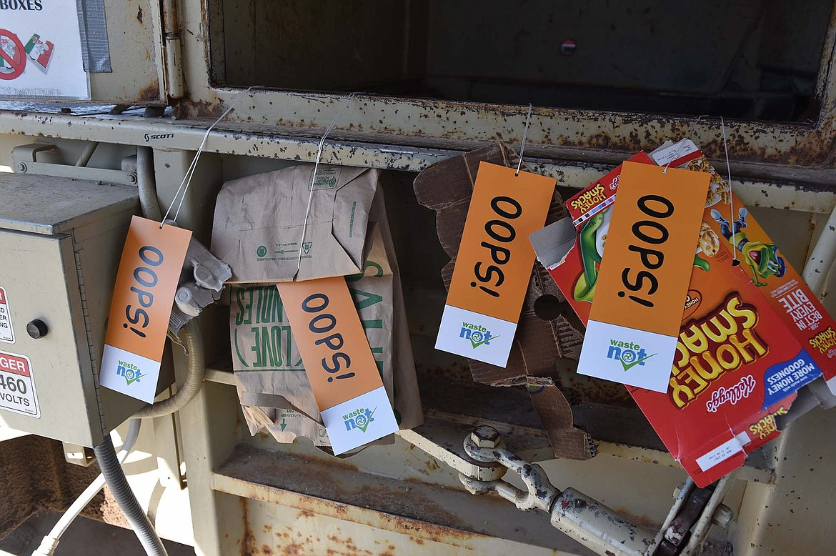 """The WasteNot Project last week for Earth Day placed """"oops tags"""" on recycling bins at Flathead County green box sites to alert folks to items that they might be placing in recycling bins incorrectly. (Heidi Desch/Whitefish Pilot)"""