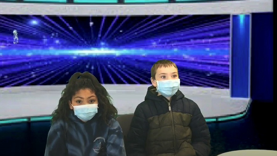 The students utilize green screen technology to appear as if they are reporting live from a real news station. Pictured is Audrey Jones and Hudson Clark.