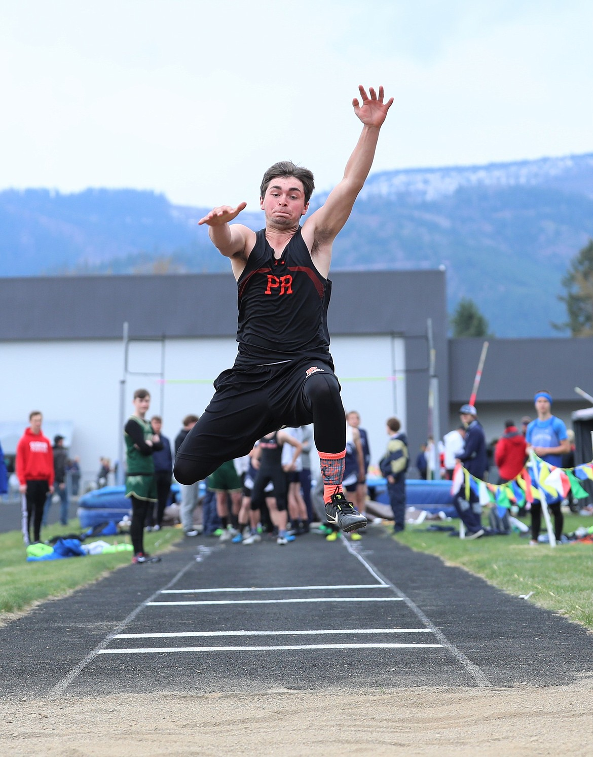 Joey Hayes leaps into the pit in the long jump.