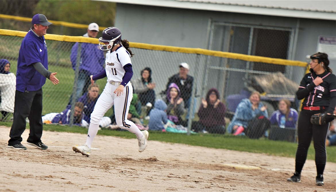 Lexy Orien greets head coach Jami Hanson at third base after hitting a two-run home run against Browning. (Scot Heisel/Lake County Leader)