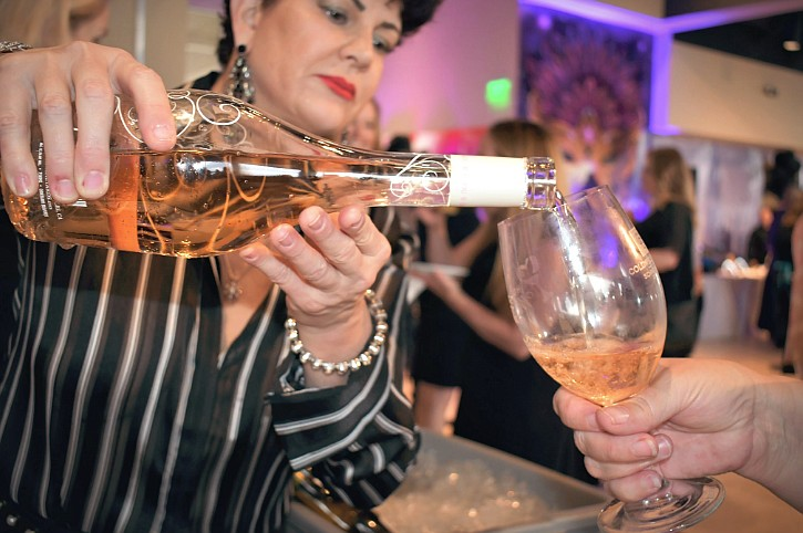 Tiffany Scattaglia, a volunteer with North Idaho Enological Society, pours Daou Rose for a guest at the the Odom Corporation table during the 36th annual Hospice of North Idaho Wine Taste and Auction in the Hagadone Event Center on Saturday. The event brought in $200,000 for the nonprofit.