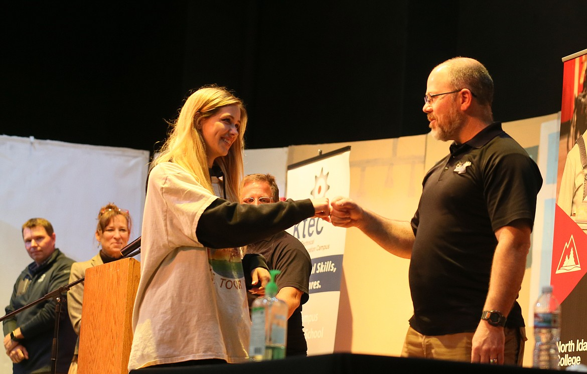 Senior Madison Brunke bumps fists with Mountain View Alternative High School Principal Paul Uzzi on Thursday during a signing ceremony in the school's gym. Seniors signed on to enroll in North Idaho College's Job Corps program while Kootenai Technical Education Campus celebrated a junior and welcomed three sophomores.