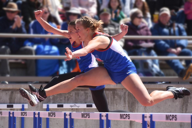 Ashlyn Savik (front) and Ellie Jordt clear the final hurdle in the 300 hurdles in Missoula Saturday. Jeremy Weber/Bigfork Eagle