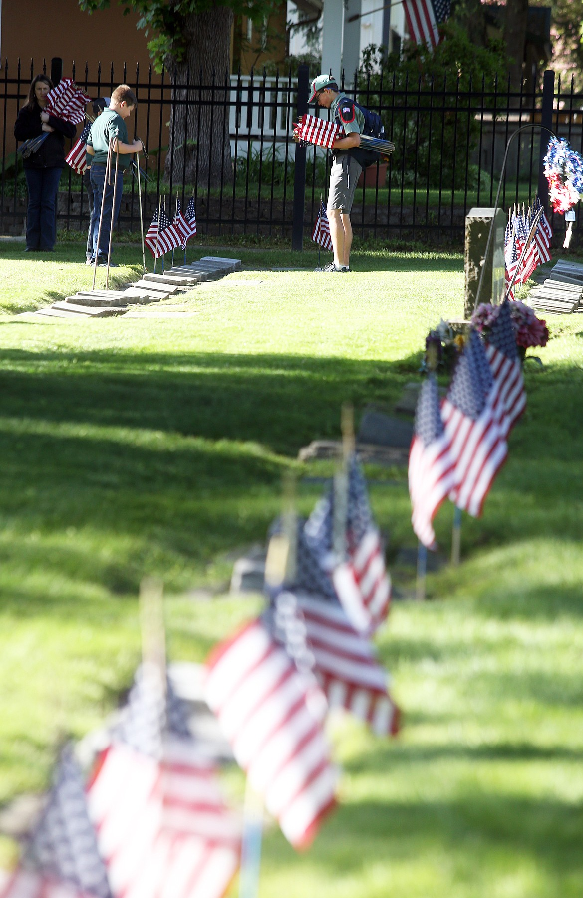 Trail Life USA youth plant flags at Forest Cemetery Wednesday.