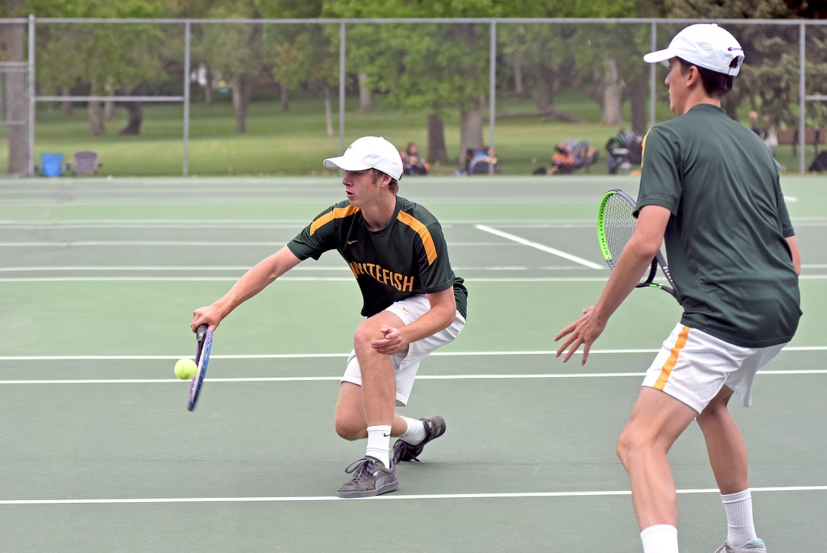Whitefish's Aaron Dicks hits a volley as as his partner Highland Lee-French watches while playing in a doubles match during the State A tennis tournament in Billings on Friday. (Whitney England/Whitefish Pilot)