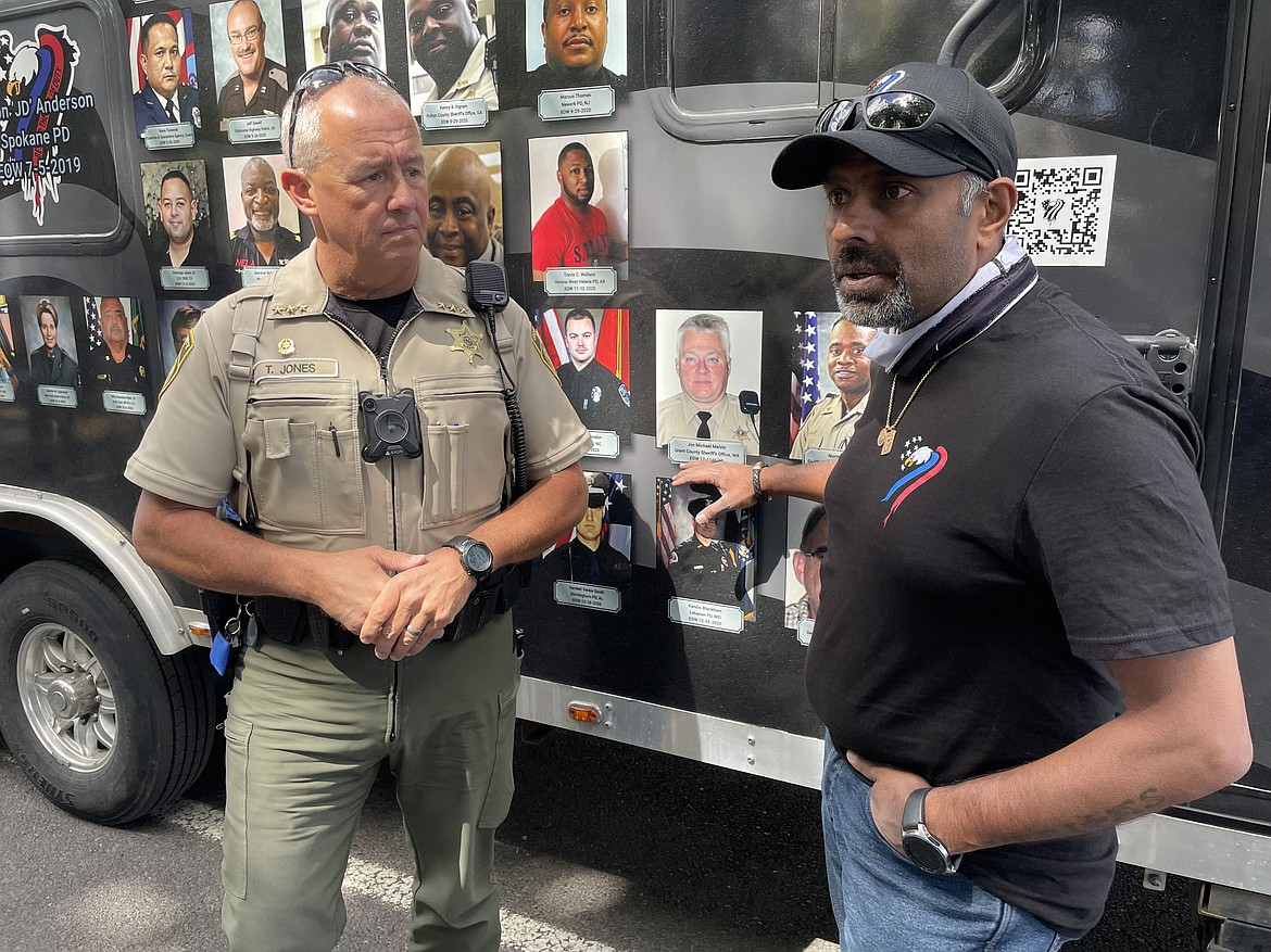 Jagrut Shah, head of the Beyond the Call of Duty Foundation, with Grant County Sheriff Tom Jones, in front of the photo of GCSO Deputy John Michael Melvin, who died of COVID-19 contracted while on the job in December 2020.