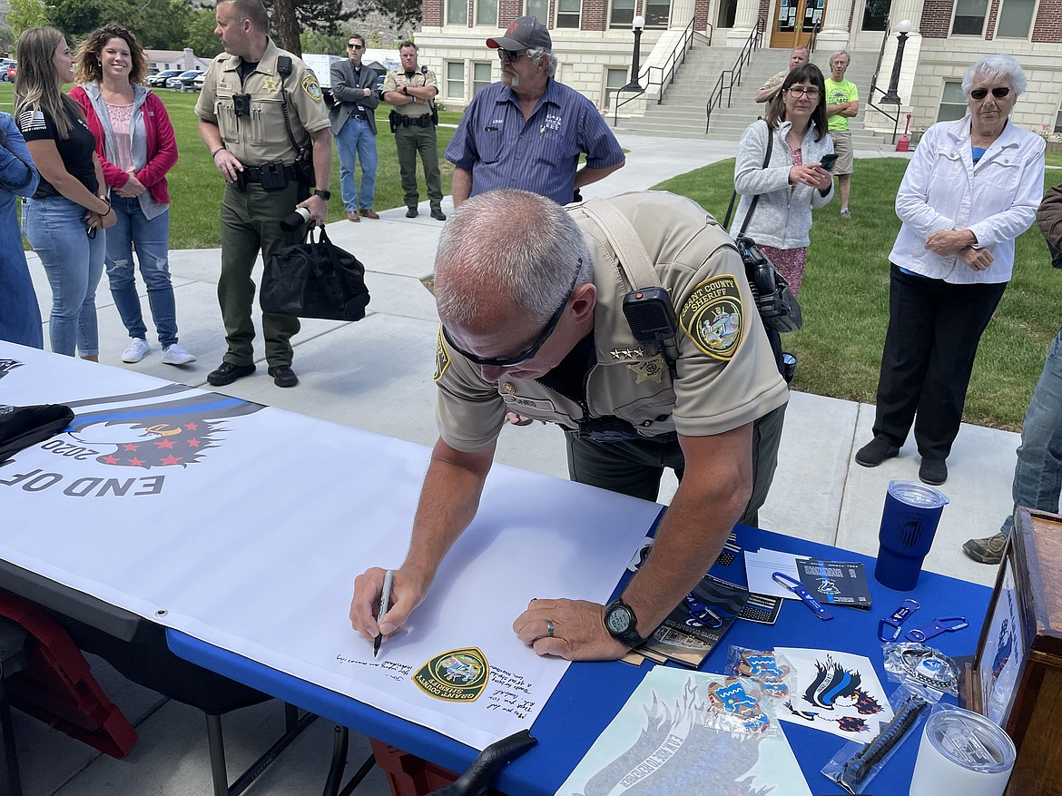 Grant County Sheriff Tom Jones signs a memorial banner on Friday as part of the End of Watch Ride to Remember.