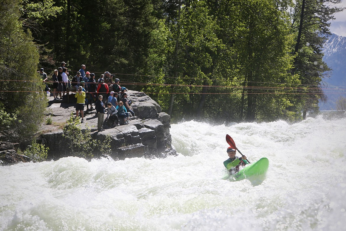 Spectators look on as a kayaker cruises down the Wild Mile during the Bigfork Whitewater Festival on Saturday, May 29. Mackenzie Reiss/Bigfork Eagle