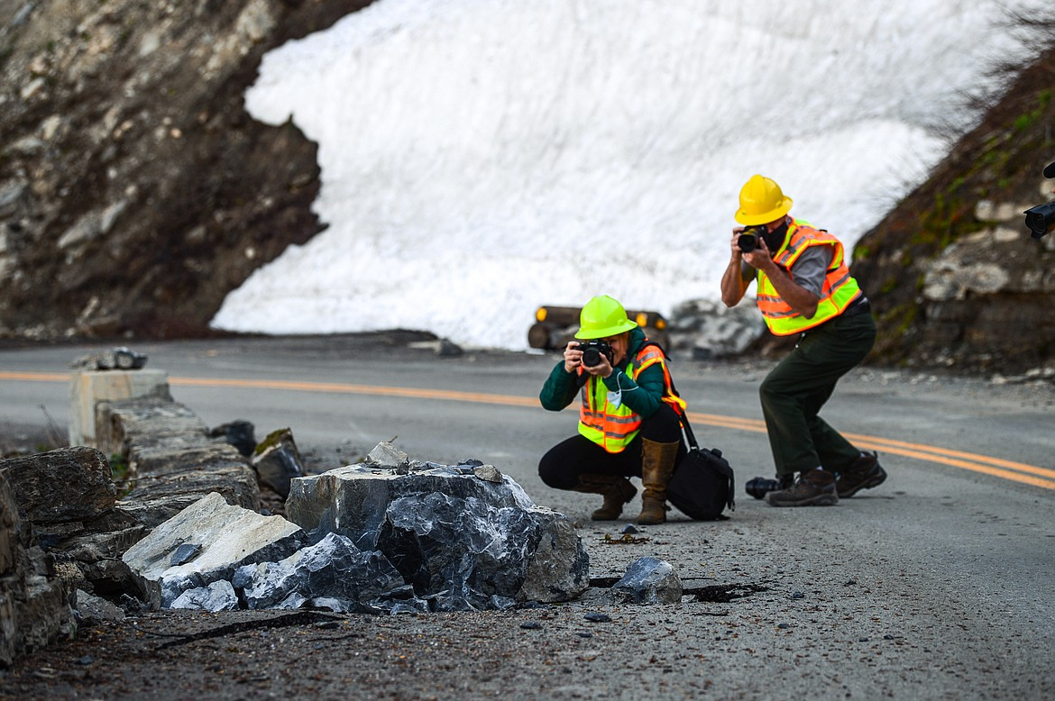 Photographers take pictures of a boulder that had fallen onto the Going-to-the-Sun Road in Glacier National Park on Wednesday, June 2, 2021. (Casey Kreider/Daily Inter Lake)