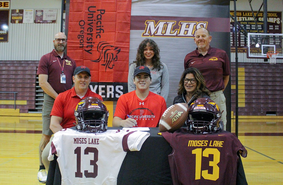 From the top left, Moses Lake assistant athletic director Clint Scriven, Savannah Ashley, football coach Todd Griffith, Justin Ashley, Everett Ashley and Kimberly Ashley gather together in the Moses Lake High School gym to celebrate Everett Ashley signing with Pacific University in Forest Grove , Oregon, to play football.