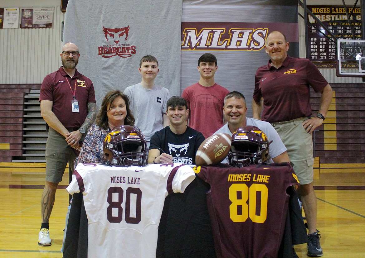 From the top left, Moses Lake High School assistant athletic director Clint Scriven, Alex Johnson, Ryan Johnson, football coach Todd Griffith, Suzanne Johnson, Brandon Johnson and Jeff Johnson gather together at the high school to celebrate Brandon Johnson signing with Willamette University to play football.
