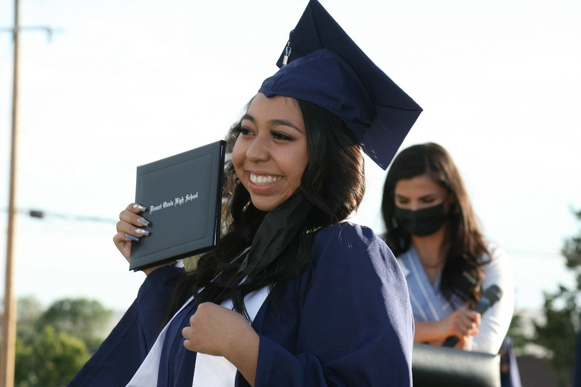 A Desert Oasis High School graduate proudly displays her diploma during ceremonies June 7 in Othello.