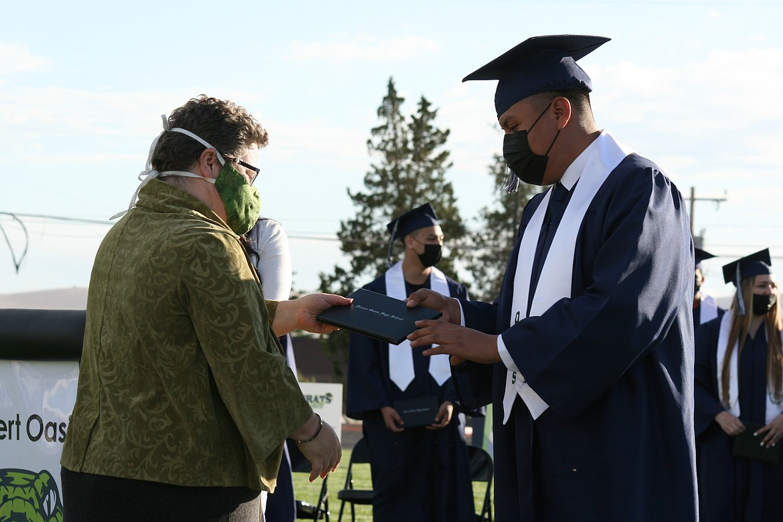 A Desert Oasis High School graduate (right) receives his diploma from Othello School Board member Jenn Stevenson (left) in ceremonies June 7 in Othello.