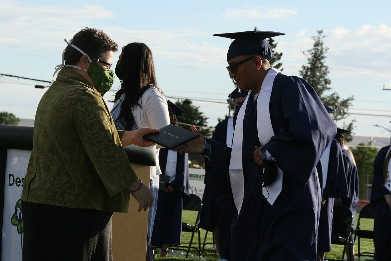 Othello School Board member Jenn Stevenson (left) hands the diploma to a Desert Oasis High School graduate during ceremonies June 7 in Othello.