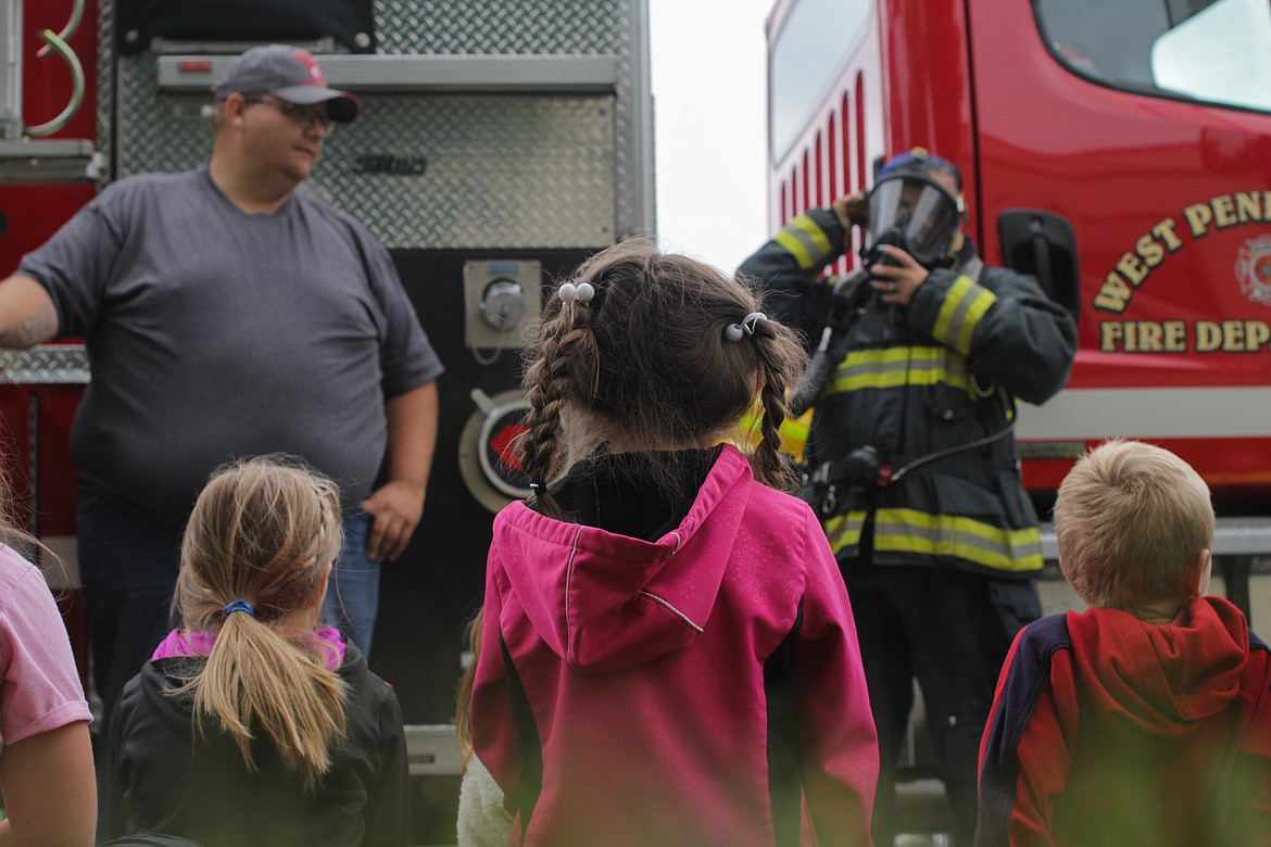 Students watch a presentation by Fire Engineer Dan Martin while firefighter Brittany Nordhagen demonstrates what a firefighter would wear to a call Wednesday at Idaho Hill Elementary.