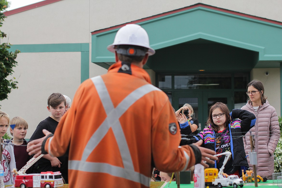 Students crowd around a miniature neighborhood as lineman James Huling presents on electrical safety Wednesday at Idaho Hill Elementary.