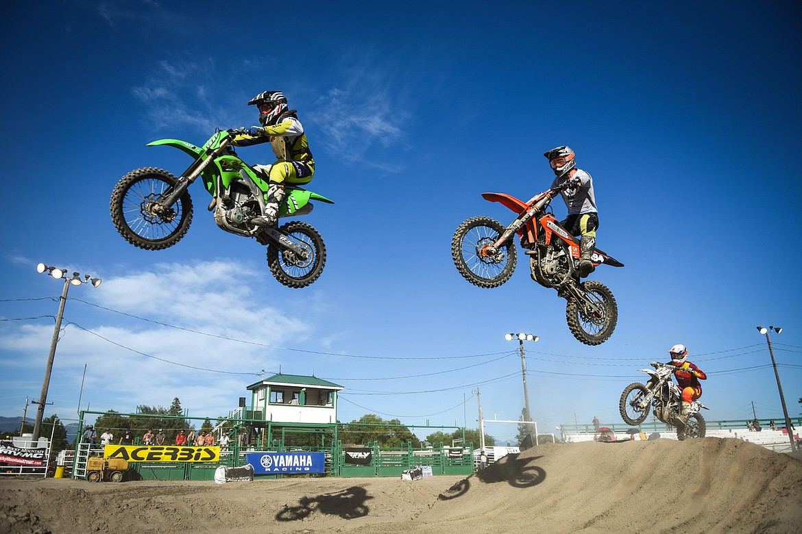 Professional riders clear a jump during Top Dawg Arena Cross at the Northwest Montana Fairgrounds in Kalispell on Friday, June 18, 2021. (Casey Kreider/Daily Inter Lake)