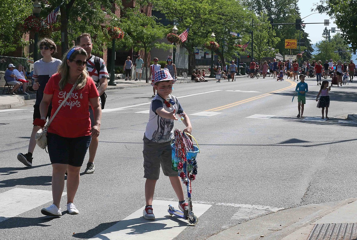 Josiah Goldthorpe, 9, of Coeur d'Alene, tosses candy to spectators Friday during the annual Kiddies Parade on Sherman Avenue.