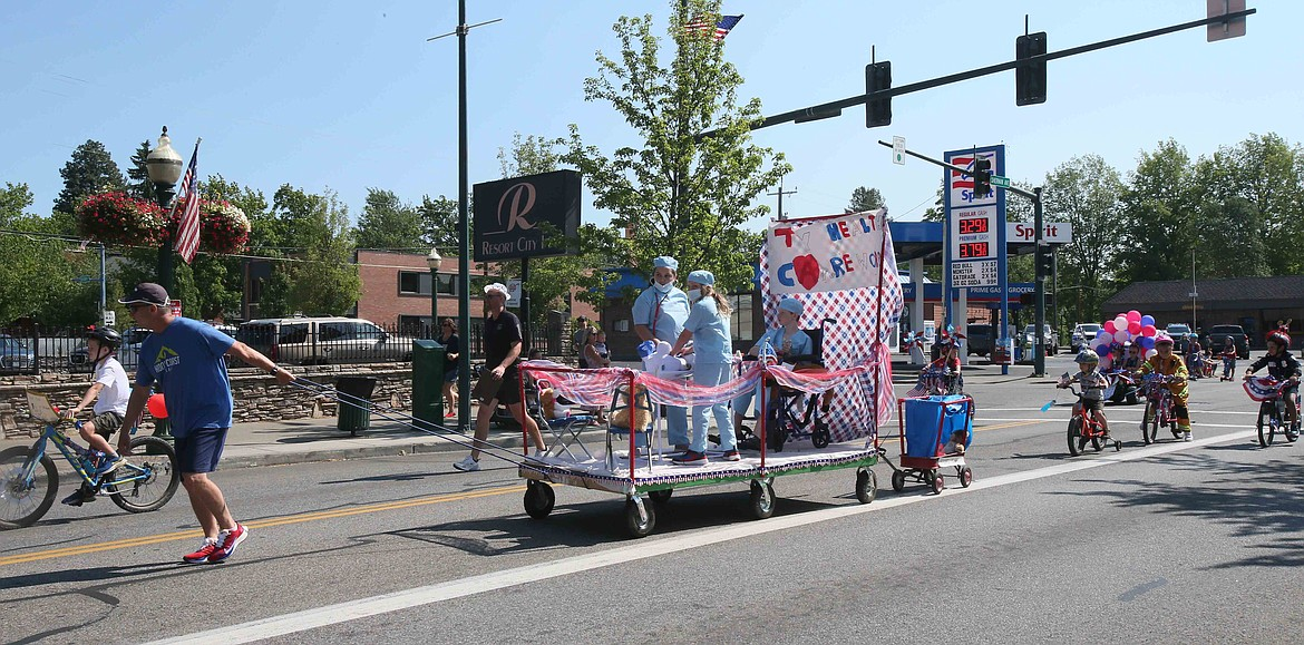 """Tristan Riplinger, Shannon Riplinger and Anna Graupman salute America's doctors and nurses with their """"Thank you health care workers"""" float in the Kiddies Parade on Friday."""