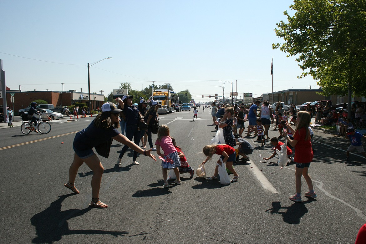 Kids scramble for hand sanitizer, thrown out by staff members from the Columbia Basin Health Association during the Independence Day parade in Othello.