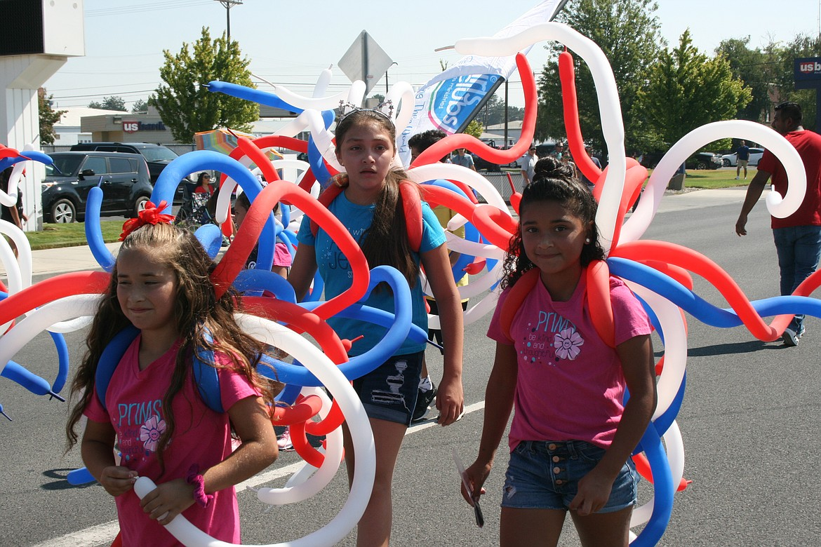 Festooned in patriotic balloons, participants march in the Independence Day parade in Othello Saturday.