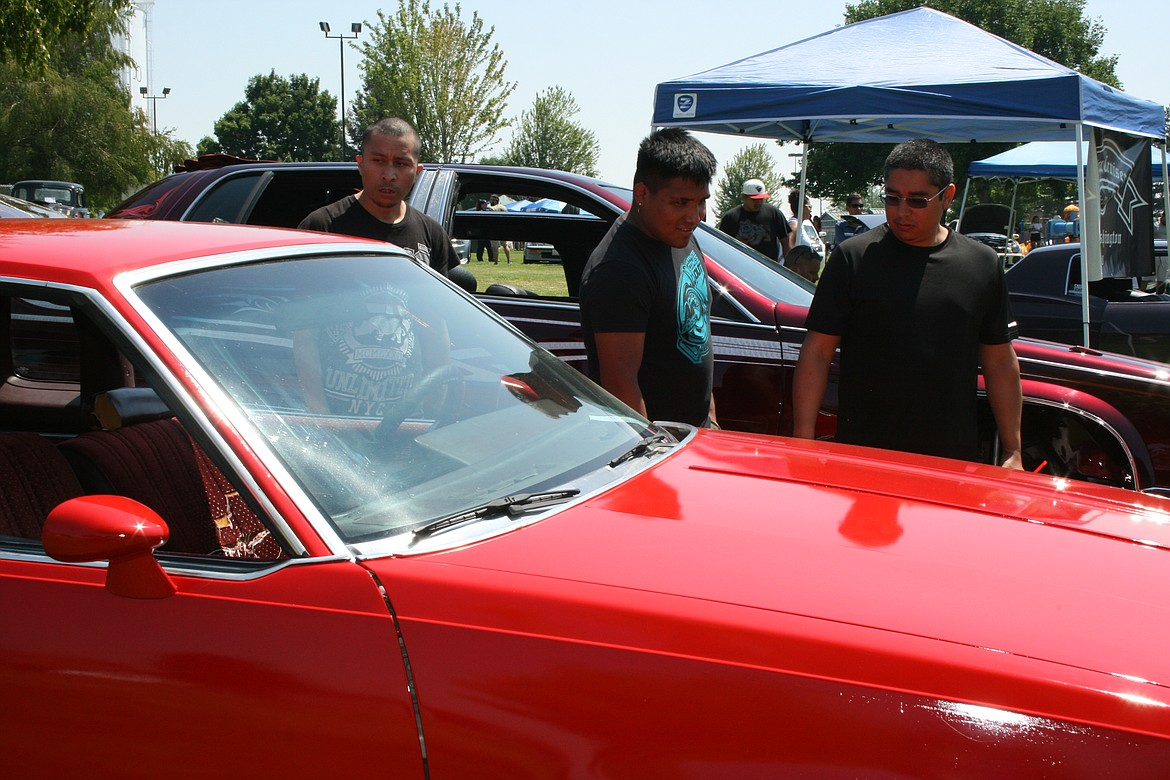 (From left) Uriel Ochoa, Eduardo Martinez and Aurelio Ochoa, all of Othello, check out the cars at the car show at the Independence Day celebration in Othello.