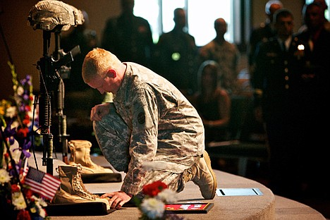 Spc. Tristan Nielsen kneels at the gear of Sgt. Nathan R. Beyers and Spc. Nicholas W. Newby during their memorial service Saturday as he gives his final salute to his fellow soldiers and friends who died July 7 in Iraq.