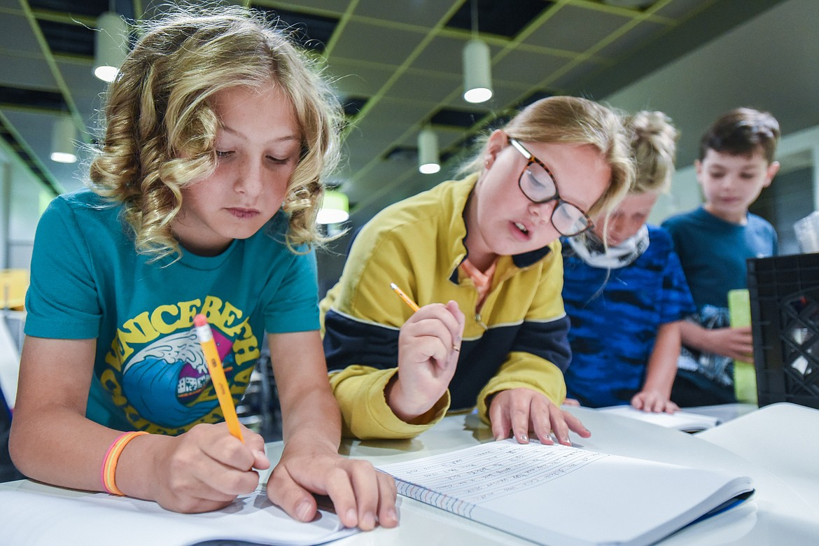 From left, incoming fourth-graders Elijah Walrath, River Knudsvig, Finn Irwin and Lucious Hatch work on a writing exercise during summer school at Muldown Elementary School in Whitefish on Tuesday, July 13. The students were given an abstract subject and asked to use adjectives and transitions to increase their writing stamina. (Casey Kreider/daily Inter Lake)