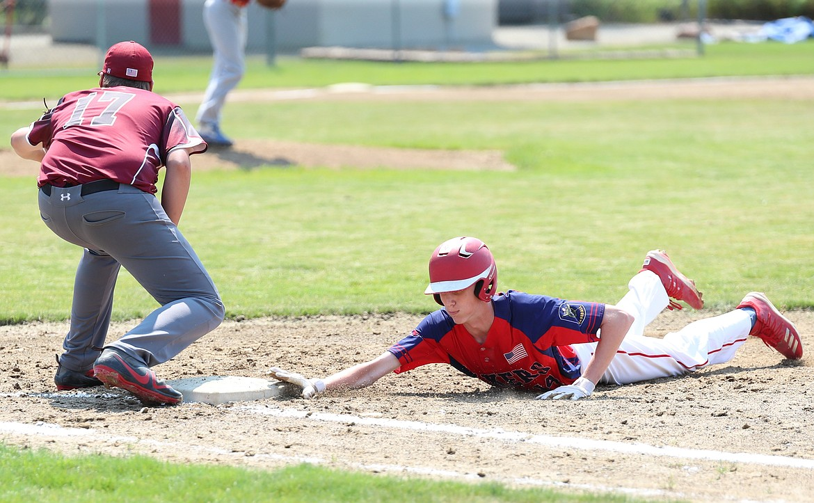 Alex Leverich slides back to first base to avoid being tagged out.