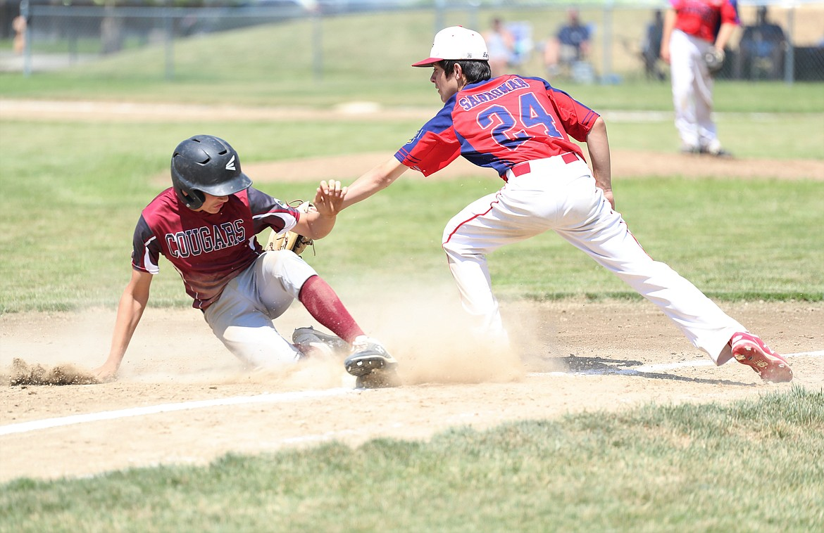 Chase Sanroman tries to tag out a Whitman County base runner at third base on Friday.