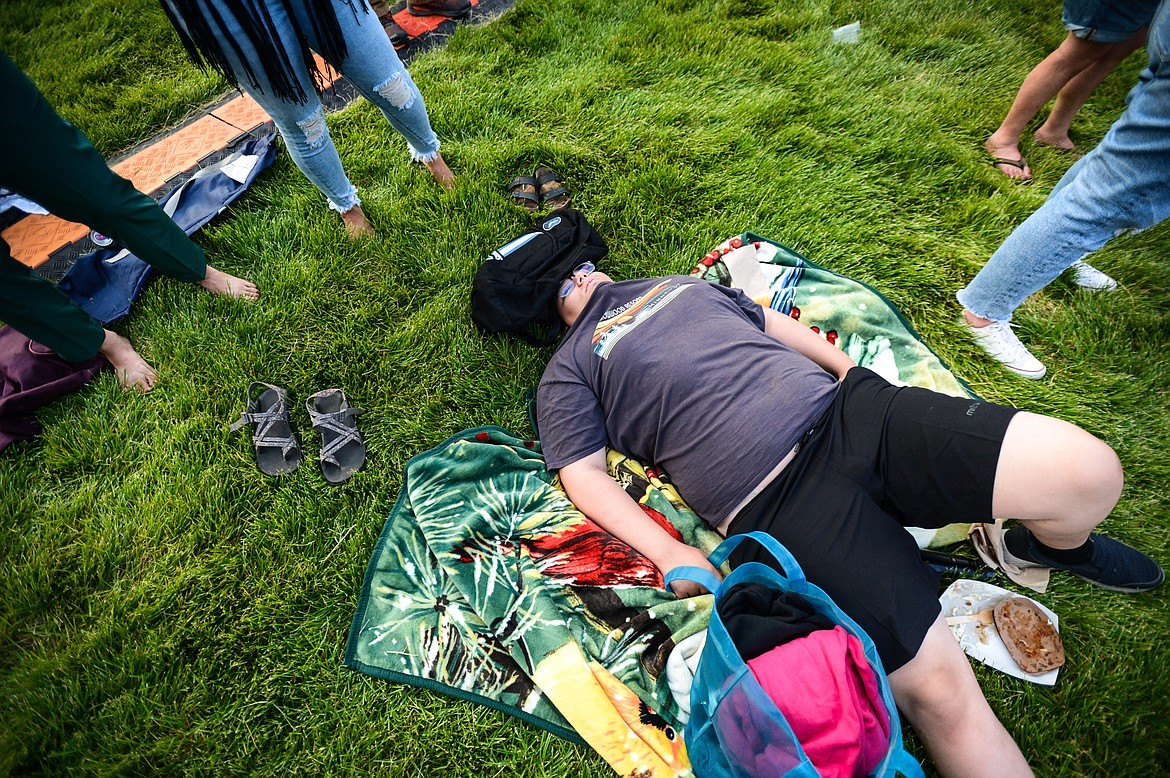 A festival-goer takes a nap on the grass near the Great Northern Stage at the Under the Big Sky Festival in Whitefish on Friday, July 16. (Casey Kreider/Daily Inter Lake)