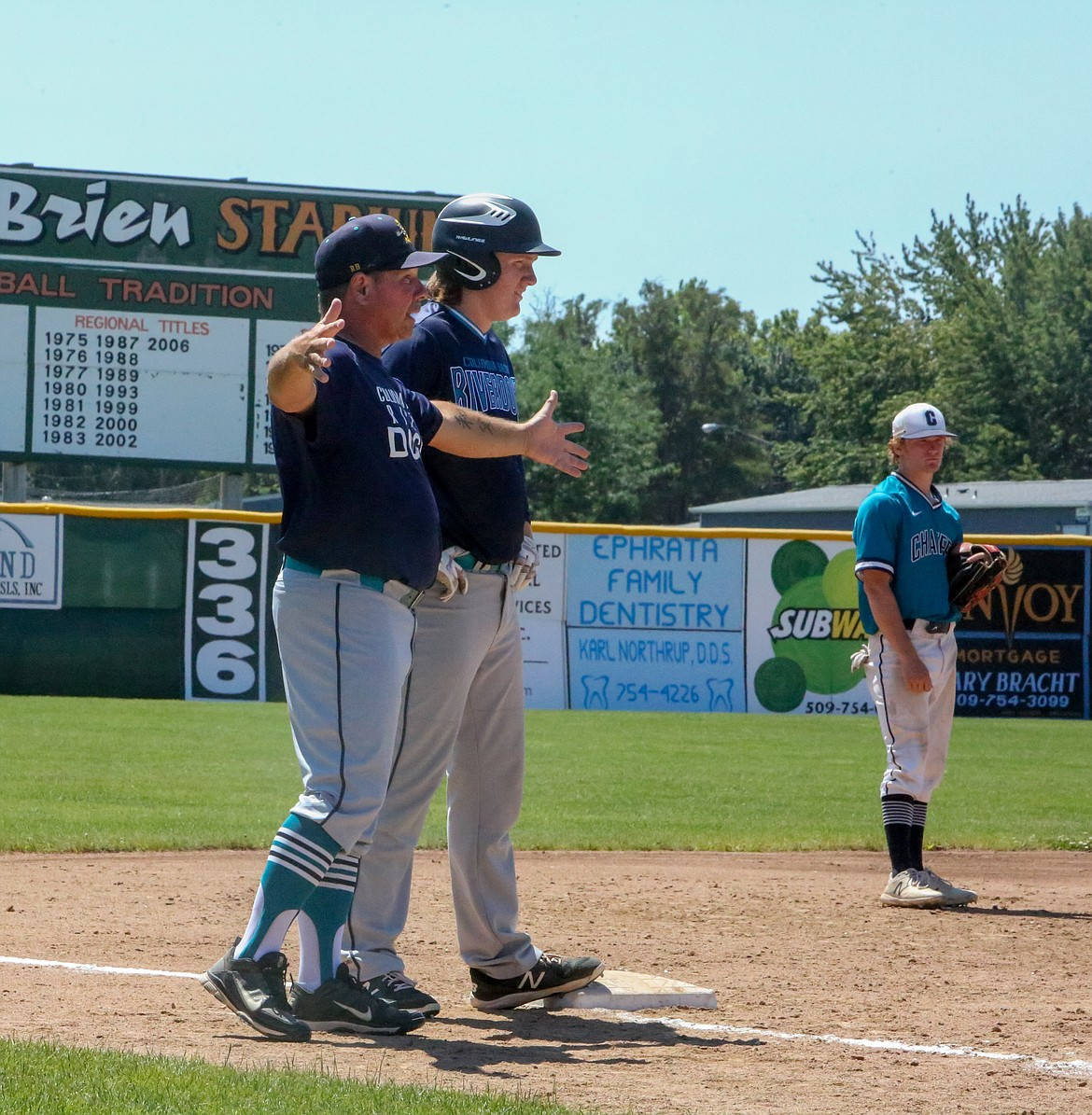 Riverdogs head coach Donnie Lindgren gives instructions to his runner on first base with Gavin Burns waiting behind him on third base Saturday morning at the Babe Ruth League Pacific Northwest 16-18U Regional Championship Tournament.