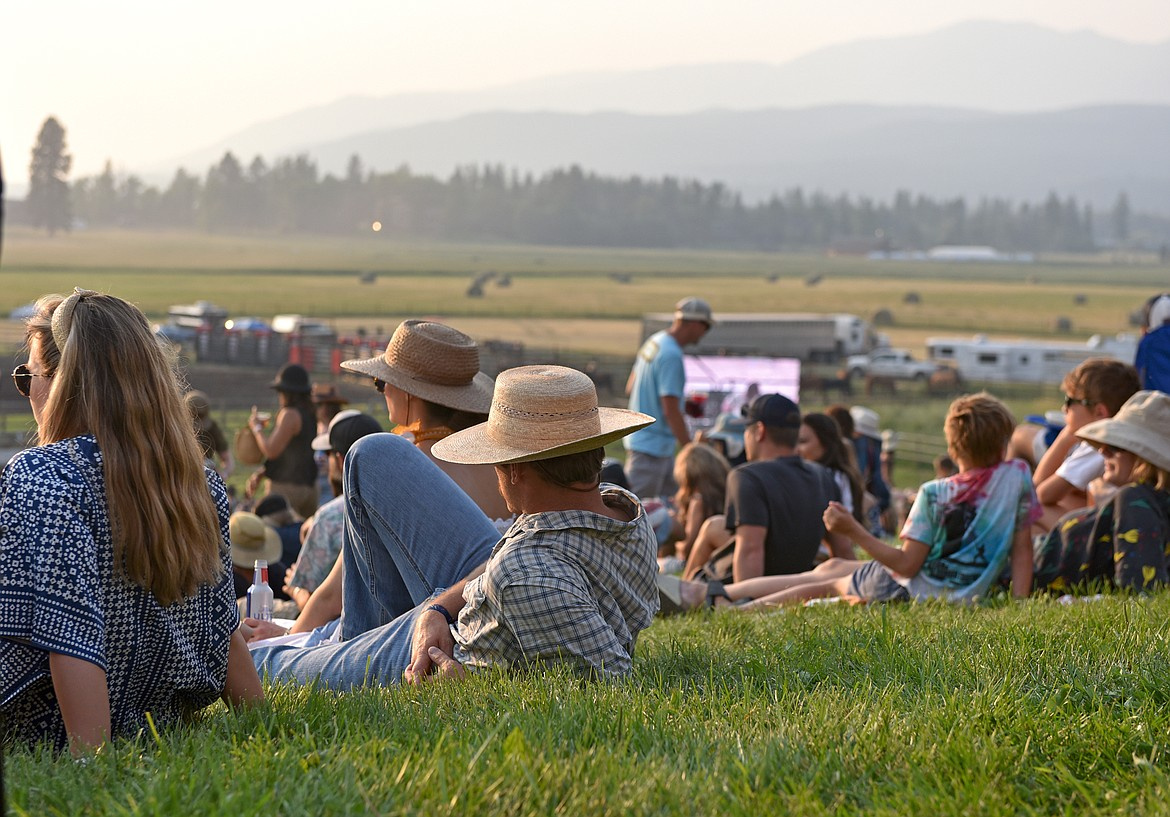 Festival goers relax on the grass while watching the musicians perform at the Under The Big Sky Festival in Whitefish on Saturday. (Whitney England/Whitefish Pilot)