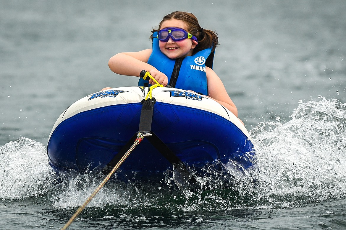 Gracie Jones, of Kalispell, flashes a smile as she rides an inflatable EZ-Ski around Echo Lake during DREAM Adaptive's Water Sports Program on Tuesday, July 20. (Casey Kreider/Daily Inter Lake)
