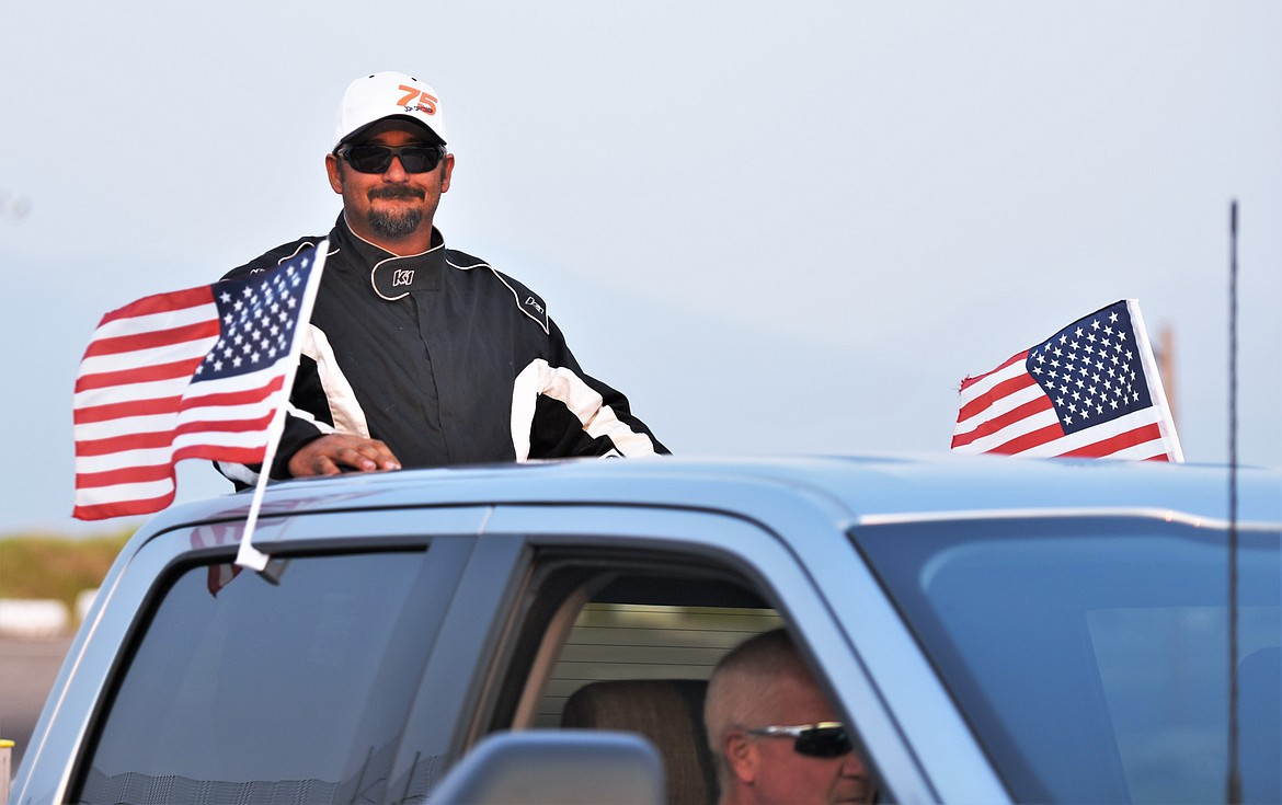 Jon Davisson of Kalispell is escorted to the track prior to the race. (Scot Heisel/Lake County Leader)