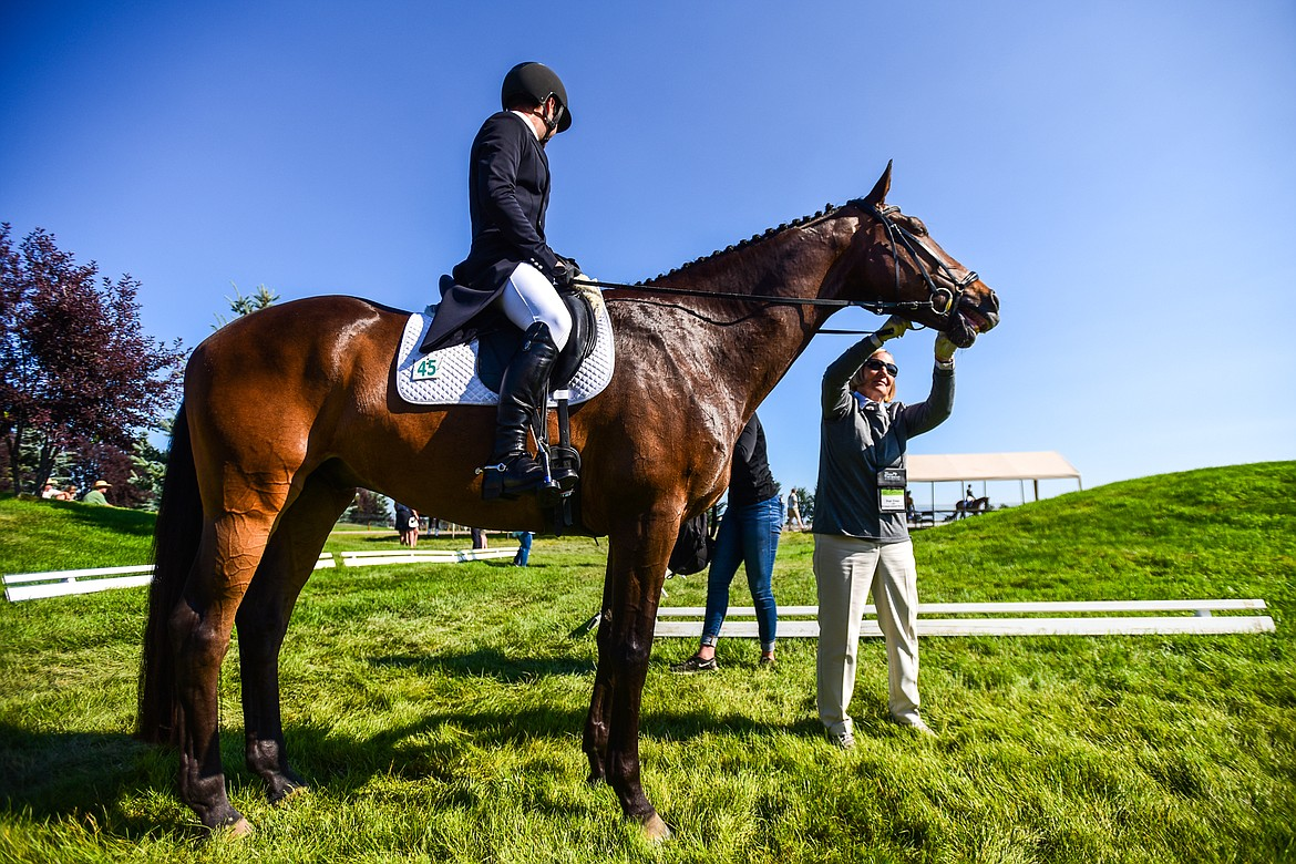 Fran Cross, right, a deputy assistant steward with The International Federation for Equestrian Sports, performs a standard equipment check after Tommy Greengard's performance on Joshuay MBF in CCI2*-Long dressage at The Event at Rebecca Farm on Thursday, July 22. (Casey Kreider/Daily Inter Lake)