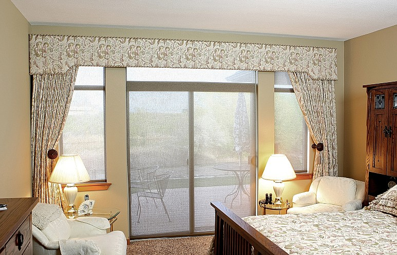 Custom matching bedspread and drapery is a popular choice for customers and can even be paired with solar shades or other window shade options pictured here.