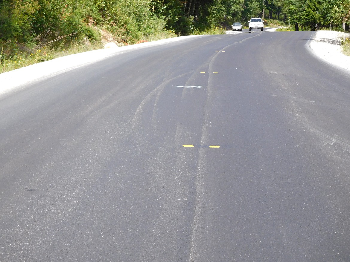 Pictured is Schweitzer Mountain Road after the repaving process. Yellow reflective thermoplastic markers identify the centerline of the road. These markers are useful for identifying the location of the centerline after other identifiers, mainly paint, is scrapped away due to heavy snow removal through the winter months.