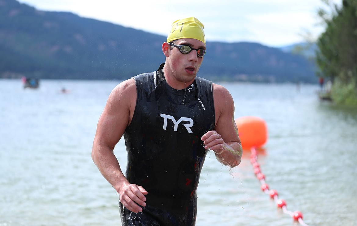 Logan Robillard, a 17-year-old from Lake City High School, runs across the line to capture first overall in the 26th annual Long Bridge Swim on Saturday. He finished with a time of 34:01.